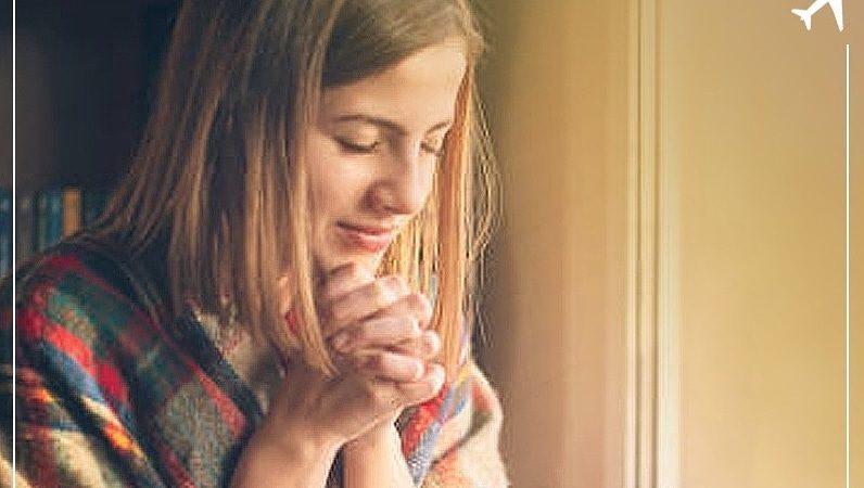 Mulher jovem reza com as mãos juntas
