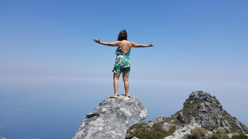 Taciana Collet está de costas, de pé, em cima de uma pedra com os braços abertos