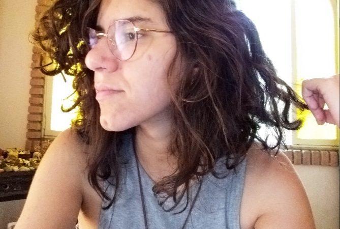 Karla segura o cabelo enquanto olha para o lado