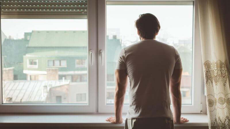 Foto de homem de costas em frente a uma janela olhando para fora
