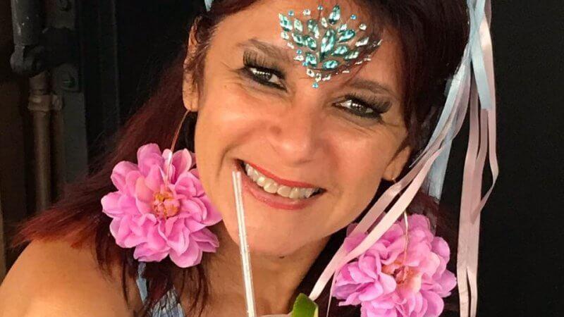 Andrea Magalhães usa tiara e brinco com flores enquanto segura um copo de bebida