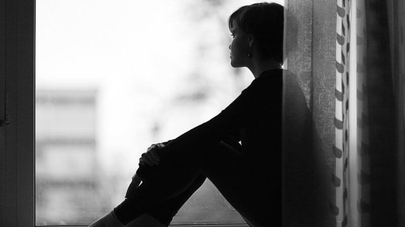 Imagem ilustrativa para o texto Eu me arrependo, mostra uma mulher sentada no parapeito de uma janela, olhando para fora
