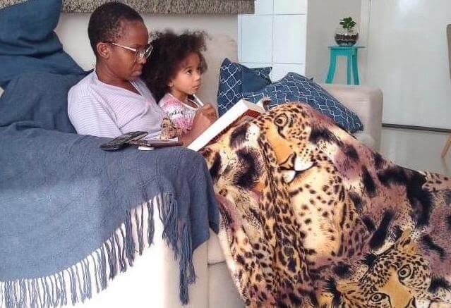 Carla Caroline na quarentena com a filha, sentadas em um sofá